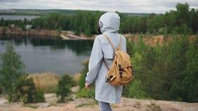Ultrarapidstående av turisten för ung kvinna med ryggsäcken som går till kanten av klippan med härlig sikt av sjön och lager videofilmer