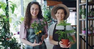 Ultrarapidståenden av gulliga blomsterhandlare för unga kvinnor som står i, shoppar med växter lager videofilmer