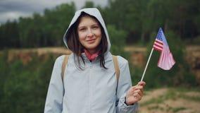 Ultrarapidståenden av vinkande Förenta staterna för den nätta amerikanska kvinnan sjunker med lyckligt leende och att se kameran lager videofilmer