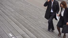 Ultrarapidvd av den stora företagsmannen som talar på trappa för smartphone- och sekreterarekvinnaklättring stock video