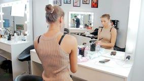 Ultrarapidvideo av den h?rliga unga kvinnliga modemodellen som applicerar makeup som ser i spegel i anletestudio arkivfilmer