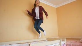 Ultrarapidvideo av den lyckliga banhoppningen för tonårs- flicka på säng arkivfilmer