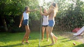 Ultrarapidvideo av gladlynta tonårs- flickor som har gyckel under vattensmå droppar från trädgårdslangen på ljus solig dag arkivfilmer