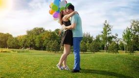 Ultrarapidvideoen av härligt barn kopplar ihop hållande massor av färgrika ballonger, och krama på parkera lager videofilmer