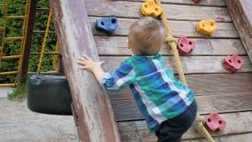 Ultrarapidvideoen av litet barnpojken som försöker att klättra på träväggen på lekplatsen parkerar in stock video
