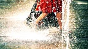 Ultrarapidvideoen av två unga kvinnor som in går, parkerar springbrunnen på en varm sommardag arkivfilmer