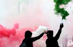 Ultras fläktar med röd vit för rök och iklädd svart för gräsplan Arkivbilder
