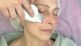 Ultrasonic face cleaning procedure. Work of cosmetician, mature woman. Slowing down skin aging stock footage