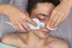 Ultrasonic face cleaning, young male. Stock Images
