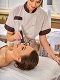 Ultrasonic facial treatment on ultrasound face machine. Woman with nude shoulders electric lift massage spa salon. Electronic stimulation female muscles. The Royalty Free Stock Photography