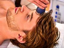 Ultrasonic facial treatment on ultrasound man face machine. Ultrasonic facial treatment on ultrasound face machine electric lift massage spa salon. Stimulation Stock Photos