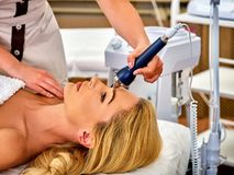Ultrasonic facial treatment on ultrasound man face machine. Royalty Free Stock Image