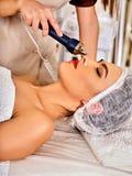 Ultrasonic facial treatment on ultrasound man face machine. stock image