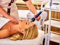 Ultrasonic facial treatment on ultrasound man face machine. Stock Photos