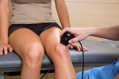 Ultrasonic therapy machine treatment doctor and woman. Patient on her knee Royalty Free Stock Image