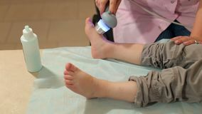 Ultrasonic treatment of the legs for a small child. Ultrasound treatment for feet the small kid in the physiotherapy room stock footage