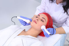 Ultrasound cavitation anti-aging, lifting procedure. Face skin care. Beautiful young healthy caucasian woman lies on a table in a medical cosmetology spa salon Royalty Free Stock Images