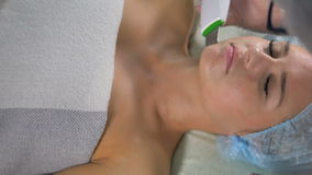 An ultrasound cleaner works on female chin. A close-up of womans chin while its cleaned with an ultrasound appliance stock footage