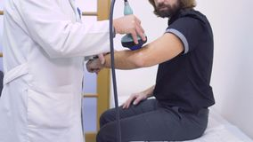 Ultrasound of elbow. Doctor examines elbow of patient with ultrasound equipment in the clinic. The man has an injury and checks the hand on the presence of stock video footage