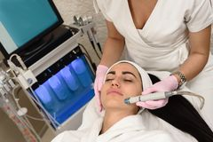 Ultrasound face peeling. Young woman having ultrasound face peeling in spa salon stock images