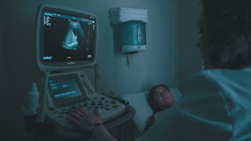 Ultrasound machine doctor`s hand usg investigation. Closeup of woman getting an ultrasound scan on abdominal by doctor. Screen of echo-cardiography ultrasound stock footage