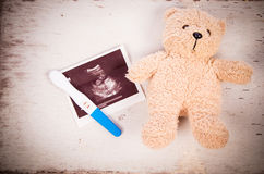 Ultrasound with pregnancy test and baby teddy bear. On wooden background stock photography