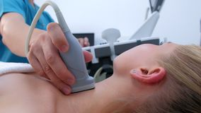 Ultrasound scanning diagnostic of woman thyroid gland in clinic, closeup view.