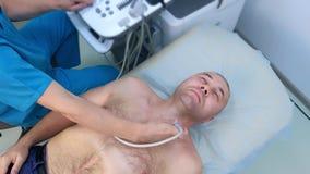 Ultrasound scanning of thyroid gland for man patient using ultrasound scanner.