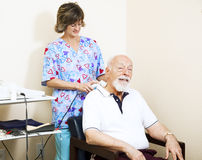 Ultrasound Therapy with Copyspace. Physical therapist in chiropractic office gives ultrasound therapy to a senior man with neck pain Royalty Free Stock Photo