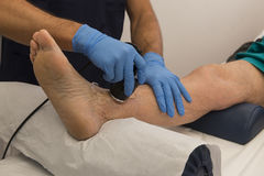 Ultrasound therapy. Gel for Ultrasound therapy on a knee of an aged man Stock Images