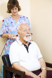 Ultrasound Therapy Relief. Senior chiropractic patient gets relief from neck pain through ultrasound technology Stock Image