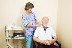 Ultrasound Therapy for Senior Man. Chiropractic nurse gives ultrasound therapy to a senior patient for relief of neck pain Stock Photo