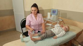 A small child lying on the couch at physiotherapy. Ultrasound treatment for feet the small kid in the physiotherapy room. A small child lies on a couch in a stock footage