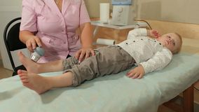 Ultrasound treatment for feet the small kid. Ultrasound treatment for feet the small kid in the physiotherapy room stock video