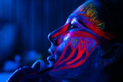 Ultraviolet black light glowing bodyart processing on young woman`s face. Pink and purple dyes in cold blue light stock photography