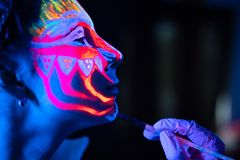 Ultraviolet black light glowing bodyart processing on young woman`s face. Pink and purple dyes in cold blue light stock image