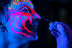 Ultraviolet black light glowing bodyart processing on young woman`s face. Pink and purple dyes in cold blue light royalty free stock photography