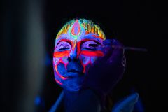 Ultraviolet black light glowing bodyart processing on young woman`s face. Pink and purple dyes in cold blue light stock photos