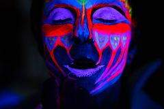 Ultraviolet black light glowing bodyart processing on young woman`s face. Pink and purple dyes in cold blue light royalty free stock image