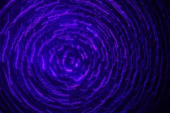 Ultraviolet Cyclone. Ultraviolet laser light cyclone spiraling in pitch black abyss with purple, magenta, and blue color Stock Images