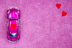 Ultraviolet toy car carries love red heart on the roof. Wedding or Valentine Day postcard invitation concept royalty free stock photo