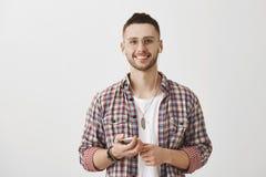 Ulubione muzyk pomoce jest produktywny podczas dnia Portret przystojny szczęśliwy caucasian facet trzyma smartphone w szkłach zdjęcia stock