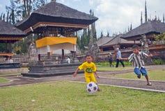 Τα παιδιά παίζουν το ποδόσφαιρο κοντά στο ναό Ulun Danau στο Μπαλί Στοκ φωτογραφία με δικαίωμα ελεύθερης χρήσης