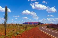 Uluru am Ende der Straße lizenzfreie stockbilder
