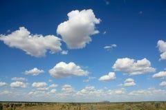 Uluru, horizon en wolken, binnenland Australië Stock Afbeelding