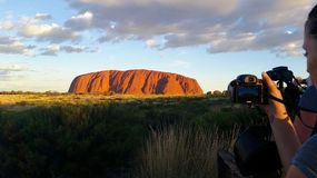 Uluru, Northern Territory, Australia 02/22/18. A photographer taking a shot of the ever changing colours of Uluru at sunset from. A designated viewing area stock image
