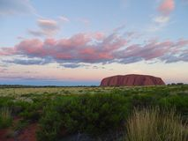 View of Uluru from the sunset viewing area. Uluru, Northern Territory, Australia 02/22/18. View of the ever changing colours of Uluru at sunset from a designated stock photography