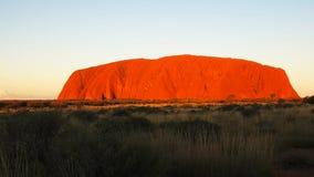 Uluru rojo brillante en la puesta del sol