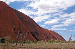 Uluru under en blått moln fylld himmel Arkivfoton