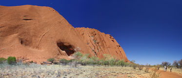 Uluru Visitors on Base Walk. A panorama of tourists on the Uluru base walk as they admire Australia's famous monolith. Uluru (Ayers Rock), Uluru – Kata Tjuta Royalty Free Stock Image